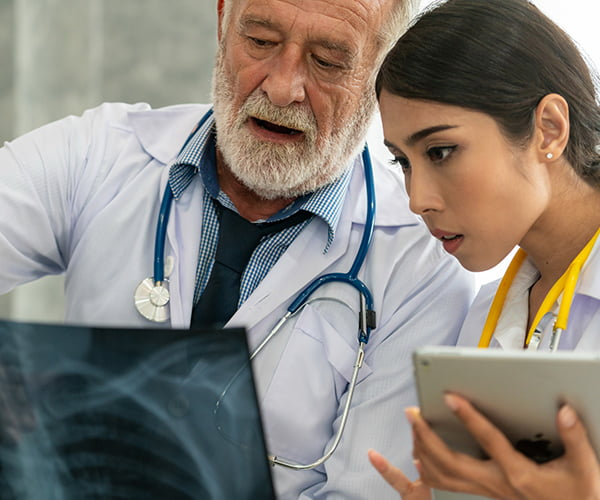 Senior team member showing an xray to a younger medical professional/doctor