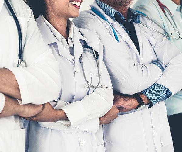 Medical team smiling shoulder to shoulder with arms crossed